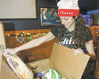 Kristen Calo, an employee of Buffalo Wild Wings restaurant in downtown Youngstown, makes sure this food box is full. Buffalo Wild Wings and Save-A-Lot stores teamed up to give out the food boxes to 200 needy families Tuesday here and in Niles.