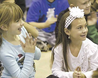 Second graders Teegan Graff, left, and Brianna DiFabio watch as the Poland High School show choir performs at Union Elementary Wednesday.