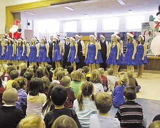 Poland Union Elementary School students watch as the Poland High School show choir performs a variety of seasonal songs.