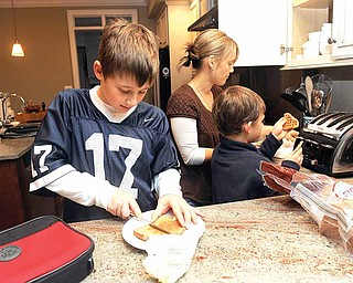 Ben DeRocco, 10, puts butter on his whole wheat bread as mom Susanna DeRocco helps Griffin, 7, toast waffles at their home in Baltimore, Maryland, on December 15, 2010.