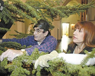 Jim Snyder and Colleen Hendel, volunteers, hang onto a bow of an 18-foot-tall blue spruce tree as its anchored in a tree holder on the altar area of St. Patrick Church on Oak Hill Avenue in Youngstown. The tree is a focal point of Christmas decor at the church.