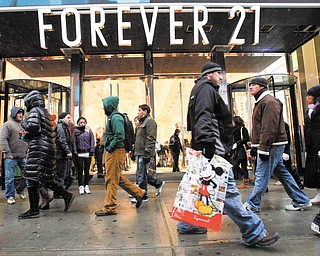 In this Dec. 26, 2010 file photo, people walk past a Forever 21 store in New York's Times Square. A new survey shows consumer confidence dipped in December, even after other reports suggest people increased their holiday spending at the biggest rate in four years.