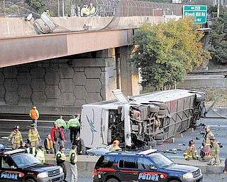 In this March 2, 2007 file photo, a charter bus carrying the Bluffton University baseball team from Ohio is seen after it plunged off a highway ramp in Atlanta, and slammed into the I-75 pavement below. The Ohio Supreme Court says a university's insurance coverage extended to the charter bus that crashed, killing five student baseball players and two others. An attorney for a Blufffton University player severely injured in the wreck says the 5-2 ruling issued Tuesday, Dec. 28, 2010, provides up to $16 million more in insurance money to pay claims.