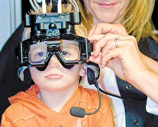 Casey Ecker, 3, has  goggles adjusted as he sits on the lap of his mother, Heidi Brandl, of Newport Beach, California, before being tested by Dr. Cara Makuta, in the Neuro Kinetics Rotational chair, which helps evaluate overall inner ear functions.