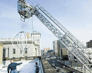 Mickey Koziorynsky, a supervisor in the Youngstown Street Department, guides the framework of the Youngstown New Year's Eve ball onto the roof of the City Hall Annex building Wednesday at Front and Market streets downtown. The Youngstown Fire Department's Ladder 22 was used to raise the 6-foot ball onto the roof because it didn't fit through a third-floor stairwell. For more information on First Night Youngstown, visit www.firstnightyoungstown.org.