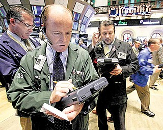 In this Dec. 2, 2010 file photo, Andrew O'Connor, second left, works with fellow traders on the floor of the New York Stock Exchange.