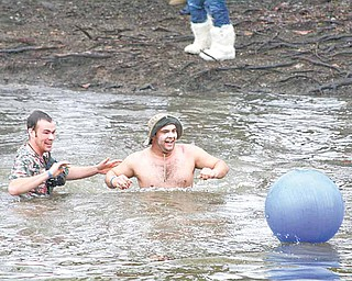 Brian Daniels of Champion, left, and Jake Waltermire of Leavittsburg wade to their beach ball in the Shenango River Saturday during the third Annual Polar Bear Jump.