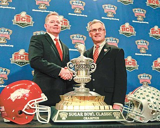 Ohio State head coach Jim Tressel, right, and Arkansas head coach Bobby Petrino, left, shake hands in front of the Sugar Bowl trophy for the upcoming NCAA football BCS bowl game in New Orleans, Monday, Jan. 3, 2011.