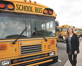 Transportation Director Colleen Murphy stands next to one of 50 Austintown school buses. The district received a grant from the Ohio EPA to retrofit 31 vehicles in its fleet.