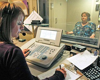 Audiologist Rebecca Price, left, tests the threshold of hearing a special tone over white noise, as Teri Kim, in a soundproof booth, responds by pushing a button at Duke Hospital's Department of Speech Pathology and Audiology in Durham, North Carolina.