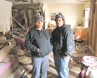 Angel Johnson, left, and her husband, Christopher Reynolds stand in  what is left of their living room at 1630 Deerfield Ave. SW, Warren,  Wednesday morning. While they were away on Tuesday afternoon, a  