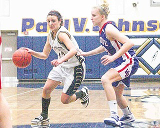 Taylor Hvisdak (12) tries to drive to the hoop as Hannah Mowery plays defense Thursday night in Lowellville.