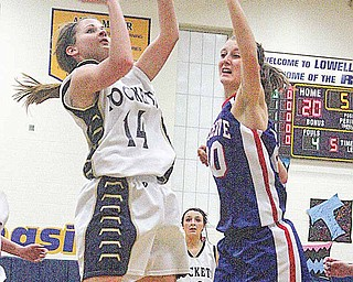 Emily Carlson (14) pulls up for two as Hannah Shrader (20) plays defense Thursday night in Lowellville.