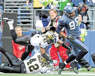 Seattle Seahawks' Cameron Morrah (88) carries the ball after a pass reception as New Orleans Saints' Roman Harper (41) and Darren Sharper (42) attempt to take him down in the first half of an NFL NFC wild card playoff football game, Saturday, Jan. 8, 2011, in Seattle. This play set the Seahawks up for a touchdown on the next play.