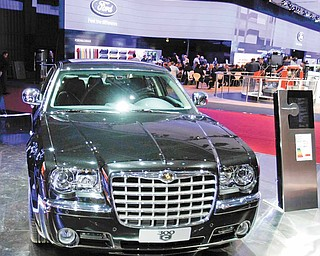 In this file photo taken Sept. 30, 2010, a model stands by the Chrysler 300 C during media day of the Paris Auto Show in Paris.