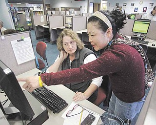Sun Gaddis, right, a career center specialist, helps job seeker Paula Morgan, of Beaverton, who has been unemployed the last nine months Friday, Jan. 7, 2011, at WorkSource Oregon, in Tualatin, Ore. The nation's economy added 103,000 jobs in December and the unemployment rate dropped to 9.4 percent last month, its lowest level in 19 months.