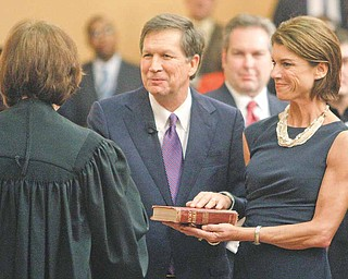 John Kasich, center, with his wife Karen, is congratulated by Justice Maureen O'Connor after bring sworn in as the new Governor of Ohio Monday, Jan. 10, 2011, in Columbus, Ohio.