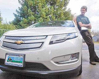 Felix Kramer, founder of CalCars, poses for a photograph next to his new Chevy Volt electric car in Redwood City, Calif., Wednesday, Dec. 29, 2010. In December, dozens of car buyers exhibited strange behaviors: They accepted the keys in front of a crowd of people, many snapping photos and taking video of the moment they picked up their new electric cars, marking the first sales of mass-produced battery-powered cars in the U.S.