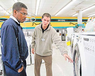 In this Dec. 24, 2010 photograph Cowboy Maloney's Electric City sales associate Bennett Chandler, right, shows off the features of a new front loading dryer to Noel Freeman of Terry, Miss., during a visit to the appliance store in Jackson, Miss. The U.S. economy ended last year on an encouraging note, with all parts of the country showing improvements. Factories produced more, shoppers spent more and companies hired more. All those signs point to a stronger economy in 2011.