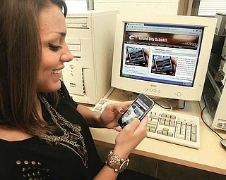 Sammy Chase, a junior at Girard Junior/Senior High School, uses her iPhone to sign up for new notification system that will alert parents, staff and students to school closings and delays. Participants have a choice of notification method — by text or e-mail.