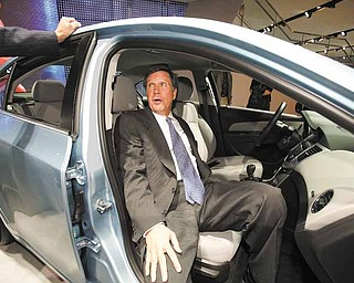 Ohio Governor John Kasich sits in a Chevy Cruze at the North American International Auto Show in Detroit.