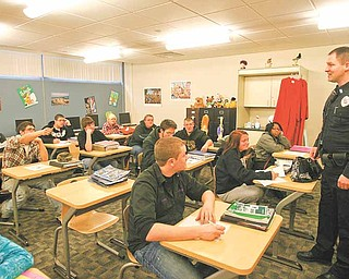 Ryan Williams, Canfield Police Department's school resource officer at the Mahoning County Career and Technical Center, talks with students in Donna Greer's English class Thursday morning. Canfield police  partnered with MCCTC and Canfield High School to implement a new drug training program geared toward young adults..