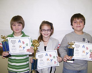 Displaying the trophies they won are, from left, Drake Beeson, second place; Skylar Sakonyi, first place; and Lukas Mosora, third place. Skylar will represent the school in Trumbull County and The Vindicator spelling bees.