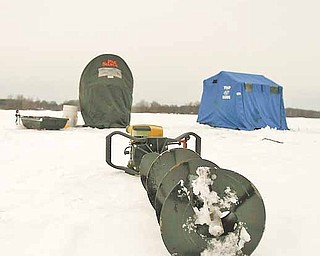 Ice Fishing is cool - A power auger for cutting through the ice sits dormant outside two ice shelters on Mosquito Lake.