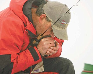 Ice Fishing is cool - water and cold weather are detrimental to equipment as John Walczak of Campbell blows on his reel to unfreeze the line.