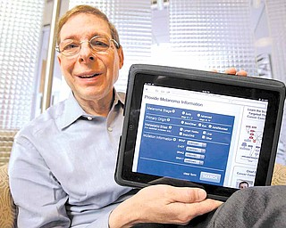 In this Friday, Jan. 14, 2011 photo, Marty Tenenbaum, a survivor of the skin cancer melanoma, shows off his free app on his iPad in his Palo Alto, Calif., office. Tenenbaum, 67, is launching a free app with Cancer Commons, a set of online tools that help professionals study the disease and help with better treatments.