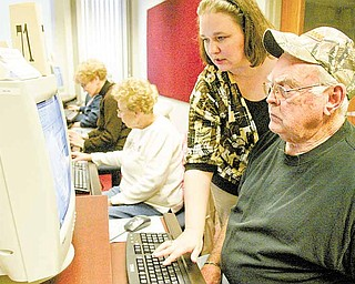 Amy Neral, teen librarian and computer instructor at Hubbard Public Library, 436 W. Liberty St., Hubbard, helps Bill Crawford of Youngstown set up an e-mail account during a free computer class offered at the library. Older residents are taking the classes to learn how to use a computer and access library services online.