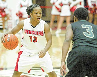 Youngstown State's Macey Nortey (13) looks to pass around Wright State's LaShawna Thomas (3) in first-half action of Thursday's game at YSU's Beeghly Center. The Penguins came up short against the Raiders when Nortey missed a 3-point shot at the buzzer to tie the game and send it into overtime. The final score: WSU 64, YSU 61.