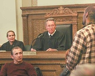 "Youngstown Municipal Judge Robert P. Milich presides over the first session of the Youngstown Veterans Treatment Court on Wednesday in city council chambers. At right is Todd Stratton, a veteran who applied to participate in the Treatment Court's program, which if completed, can keep him from going to jail. Looking on is Ohio Supreme Court Justice Evelyn Stratton and former professional boxer Ray ""Boom Boom"" Mancini, who is interested in veterans issues."