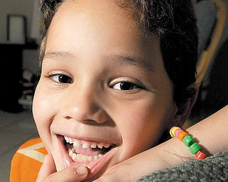 Raul Estrada, 6, of Hialeah, one of Dr. Jeffrey Blum's patients, points out the two bottom permanent teeth that grew in where he had two baby teeth harvested by Dr. Blum who sent them to New York, where they will be stored so they can reap their stem cells.