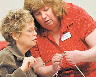 Sandra Horforth, right, a clerk at Hubbard Public Library, 436 W. Liberty St., shows Nancy Bolchalk of Hubbard how to hold fingers and yarn to get the correct stitch in her knitting. Horforth volunteers her time to lead the Fortnightly Craft Group at the Hubbard Public Library..