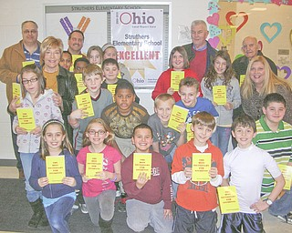Encouraging words: Struthers Rotarians continued the club's participation in a Dictionary Project recently by delivering dictionaries to fourth-grade students at Struthers Elementary School. The purpose of the program is to help fourth-graders in all area schools become good writers, active readers, creative thinkers and resourceful learners. Joining the elementary school students as they display the dictionaries they received as gifts are, at back from left, Tom Baringer, Marge Diorio, Bryan Higgins, Dan Becker and Paul Paris, Rotary members, and Maggie Kowach, school principal.