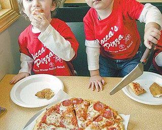 William D. Lewis|The Vindicator  Brothers Enzo Cocca, 3,left, and Rocco Cocca, 1, whose family owns Cocca's Pizza dig into an old family favorite. Cocca's is planning to open its 5 th pizzeria in Poland.