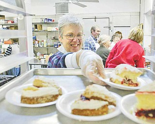 St. Vincent DePaul Society dining room volunteer Joanne Roberts reaches for a dessert.