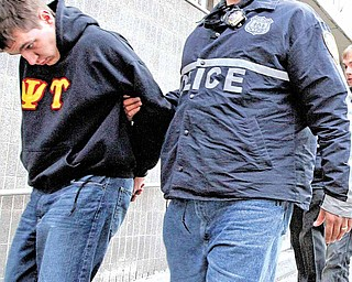 Columbia University student Michael Wymbs, left, is escorted from the New York Police Department's 25th Precinct in Manhattan after he and four other students were arrested on Tuesday Dec. 7, 2010, in New York. Authorities say the five Columbia University students sold LSD-spiked candy and a full menu of other drugs at three fraternity houses and other residences on the Ivy League campus, where it was believed at least one of the suspects was using the drug money for school expenses.