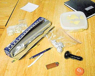 In this Tuesday, Dec. 7, 2010 photo released by the Office of the Special Narcotics Prosecutor for the City of New York, candy wrapped in foil is seen in the plastic bag at right and individual bags of capsules believed to be MDNA are seen at left, on a table in the Columbia University student housing, in New York. Five Columbia University students were charged Tuesday, Dec. 7, 2010, with selling LSD-spiked candy and other drugs at three fraternity houses and other residences on the Ivy League campus, with two allegedly claiming they needed the drug money to cover tuition.