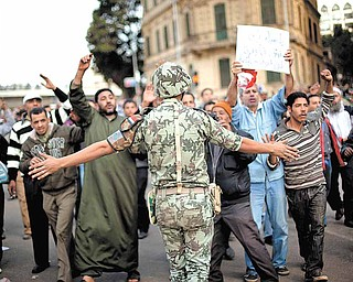 An Egyptian army soldier tries to stop anti-government protesters as they walk towards Tahrir Square in Cairo, Sunday, Jan. 30, 2011. The Arab world's most populous nation appeared to be swiftly moving closer to a point at which it either dissolves into widespread chaos or the military expands its presence and control of the streets.