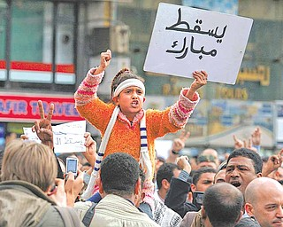 "A girl holds a sign reading ""Down with Mubarak"" during a demonstration in Cairo, Sunday, Jan. 30, 2011. The Arab world's most populous nation appeared to be swiftly moving closer to a point at which it either dissolves into widespread chaos or the military expands its presence and control of the streets."