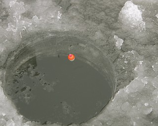 ROBERT K. YOSAY | THE VINDICATOR..Ice Fishing is cool - a small bobber sits on the whole drilled thru the ice  as very light fishing line and tackle are used during the winter ice fishing season... Ó--30-..