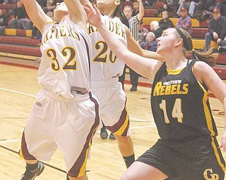 Emily Seman (32) grabs a rebound as  Samantha Smith (20) and  Gerie Sickle (14) try to get in on the play Monday night in South Range.