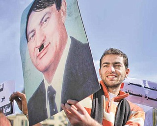 An anti-government protester being carried on the shoulders of another holds up a portrait of Egyptian President Hosni Mubarak on which he had drawn a moustache and hair in black to represent Adolf Hitler, to loud cheers from the crowd, at the continuing demonstration in Tahrir square in downtown Cairo, Egypt, Monday, Jan. 31, 2011. A coalition of opposition groups called for a million people to take to Cairo's streets Tuesday to demand the removal of President Hosni Mubarak.