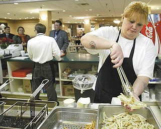Theresa Smith, who works at the Capitol Grill in the 20 Federal Place food court, prepares french fries during the afternoon lunch crowd at the downtown Youngstown office building.