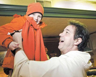 The Rev. Greg Maturi, pastor of St. Dominic Church, lifts 5-year-old Jack Neill into the air at The Boulevard Tavern on the city's South Side. Members of St. Dominic and St. Patrick churches gathered at the Southern Boulevard restaurant Tuesday evening to get to know one another.