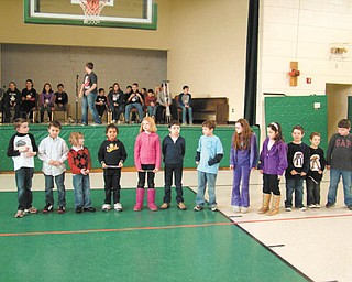 Audience is spellbound: Although they were too young to compete in the official spelling bee at St. Patrick School in Hubbard, this group of students from grades one through three lined up to demonstrate their spelling skills as older students, in the background, prepared for the local spelling bee. Family, friends and classmates were held spellbound as the youngsters competed for the first time in a classroom spelling bee. The winner of the competition was Luke Yungbluth, a student in the third grade taught by Joann Matune.
