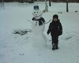 4-year-old Joshua Guy builds his first snowman at the Poland home of his grandparents, James and Sandra Guy.