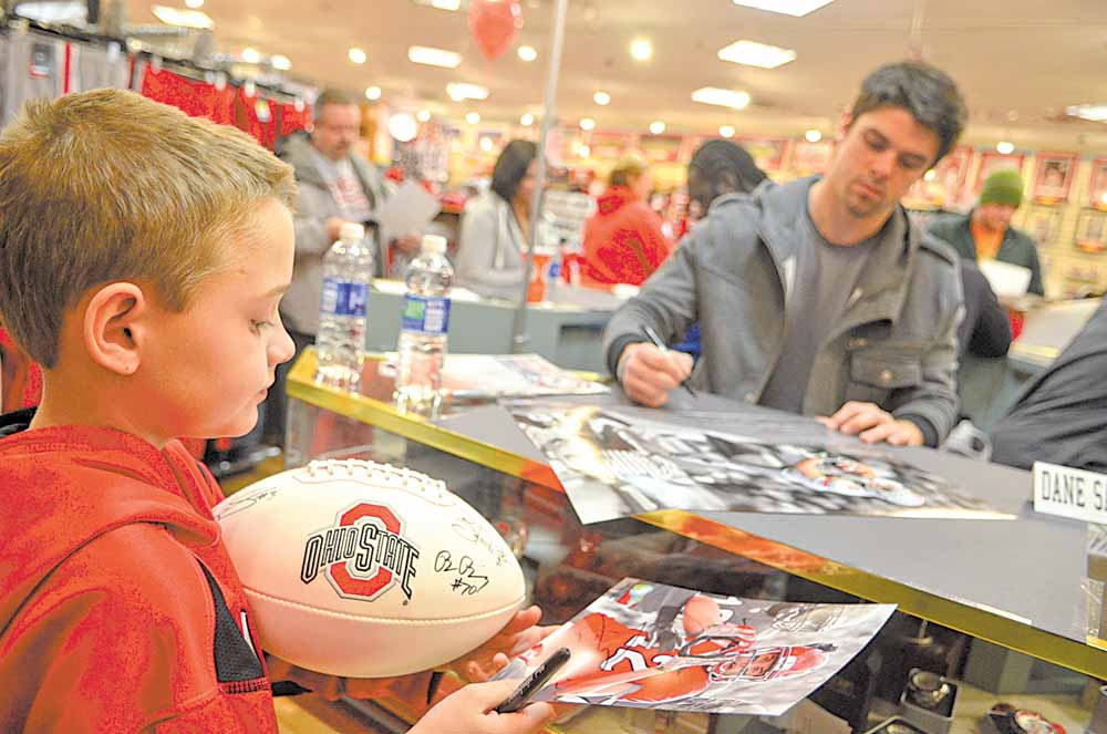 "Peyton Weaver of Middlefield walks away with a poster, photograph and football autographed by Ohio State University wide receiver Dane Sanzenbacher, in background. Although only 9, Peyton claims to have been fan of OSU ""forever."""
